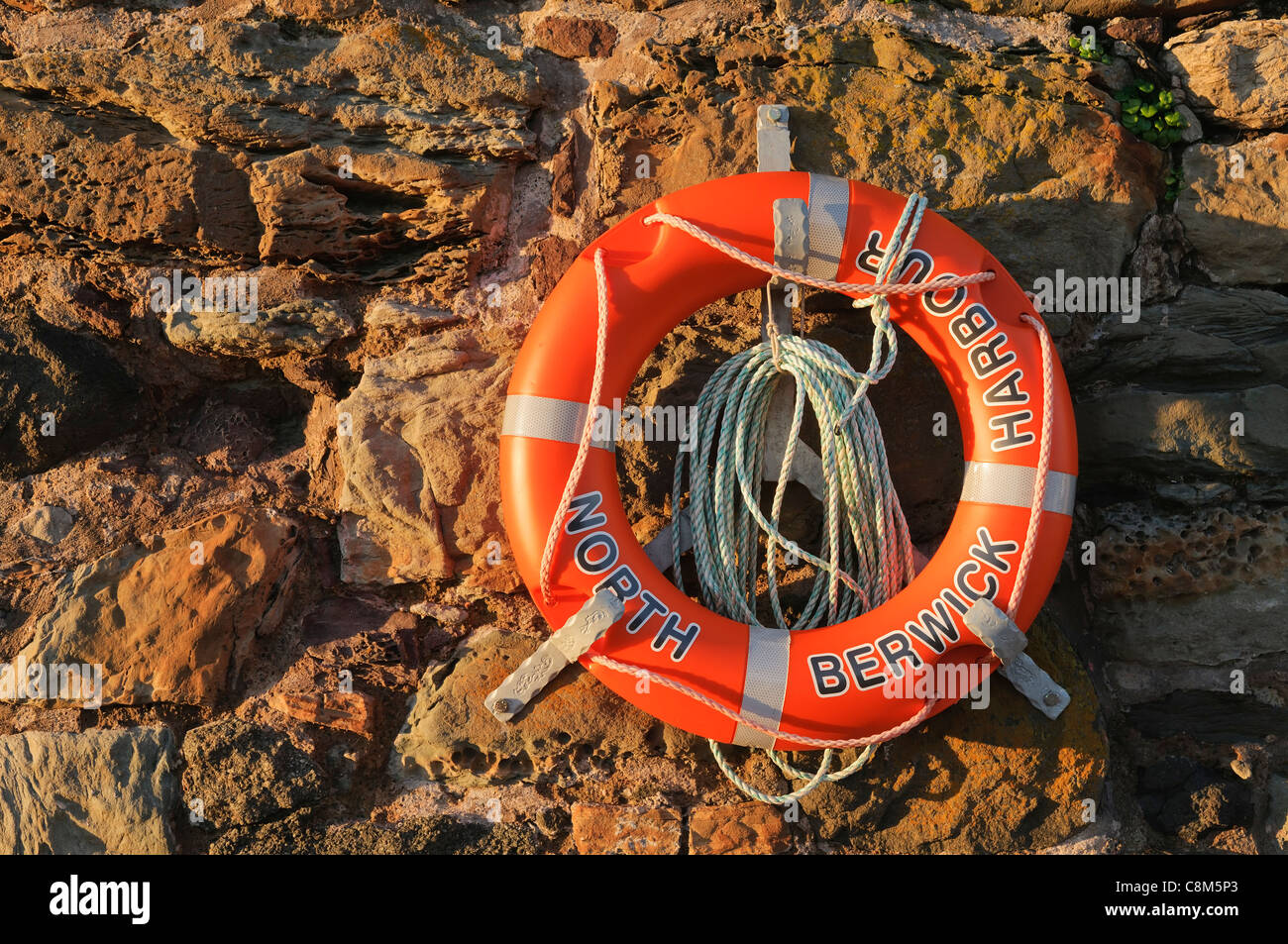 Orange lifebelt (sometimes called a lifebuoy) at the harbour in North Berwick, East Lothian, Scotland. - Stock Image