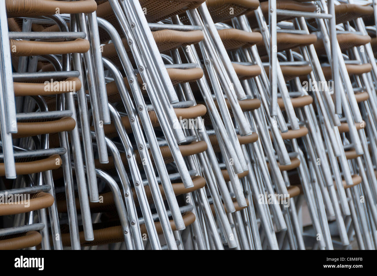 Aluminium chairs stacked outside a cafe. - Stock Image