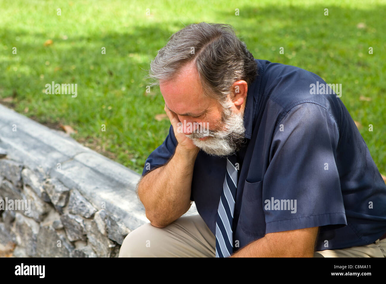 Businessman depressed by economic conditions sits melancholic in a park with his head in his hand. - Stock Image