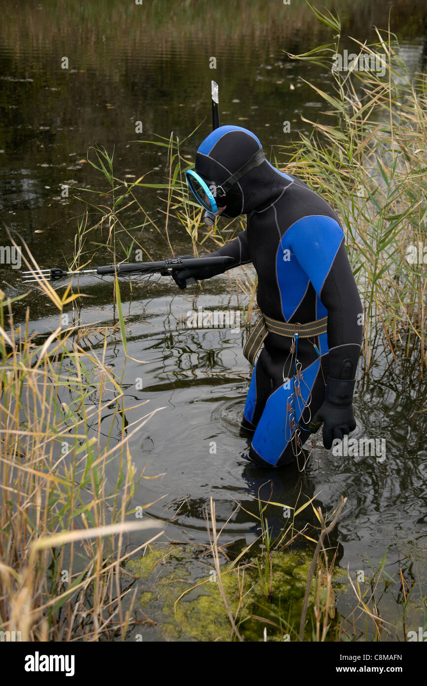 Underwater hunter is immersed in water to hunt . Stock Photo