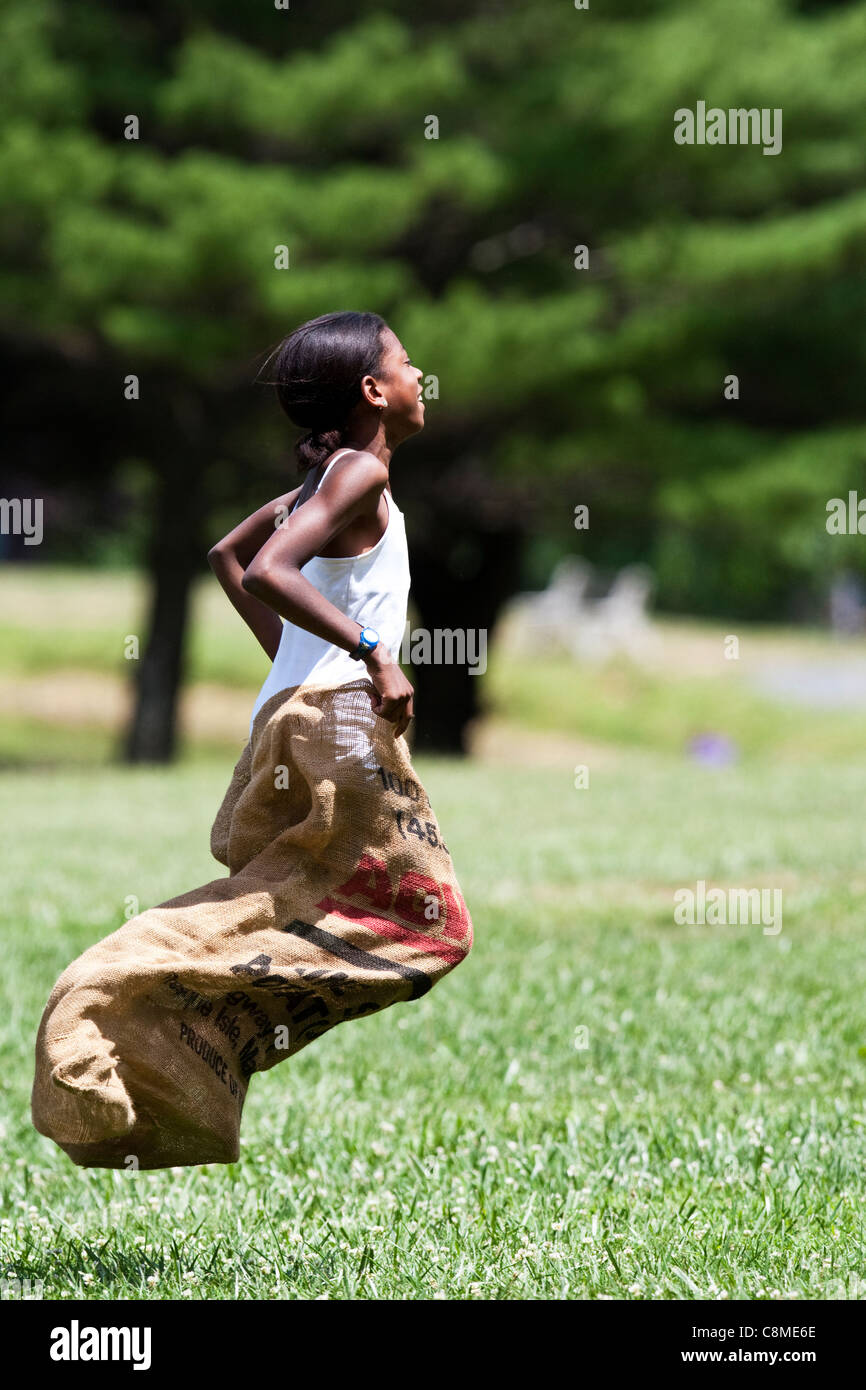 Young black female child in potato sack race. - Stock Image