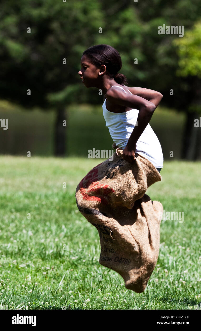 Young black child in potato sack race - Stock Image