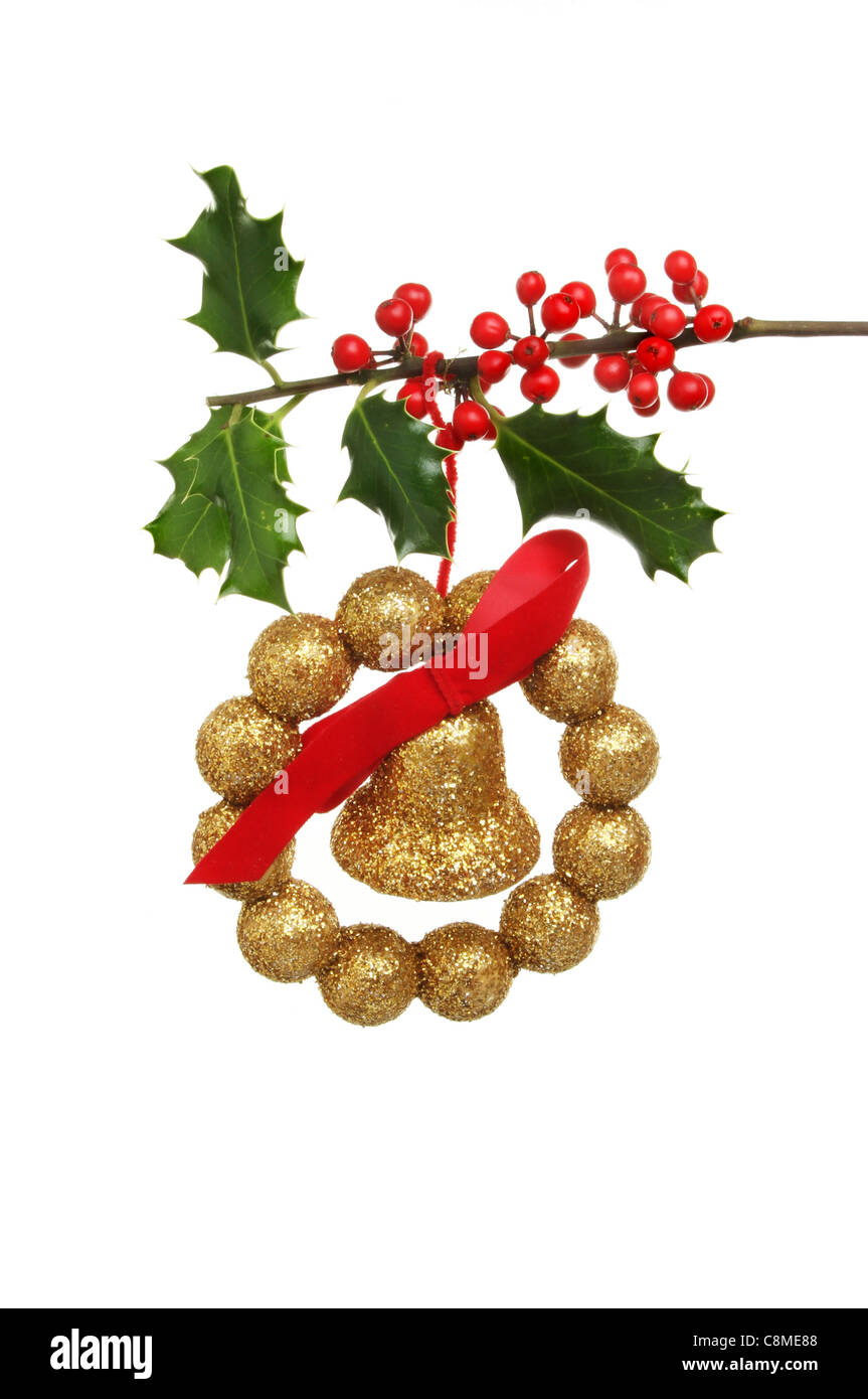 Christmas Decoration Of Gold Bell Bow And Balls Hanging From A Fruiting Holly Bough