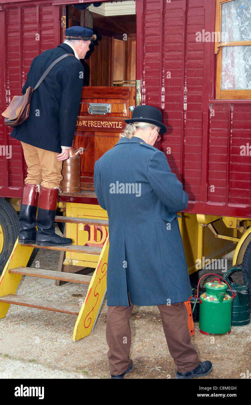 Two people in Edwardian clothing inspect a traveling showman's living van. Their appearance suggests bailiffs - Stock Image