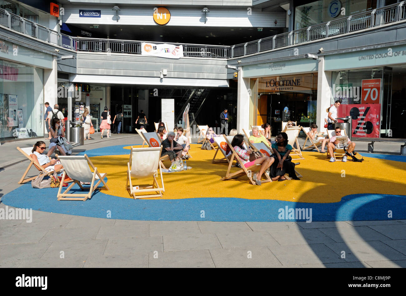 People relaxing in deckchairs on imitation sand at the N1 Centre, Angel Islington London England UK - Stock Image