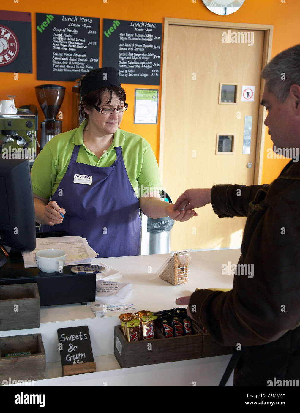 Man purchasing a sandwich at a coffee shop. - Stock Image