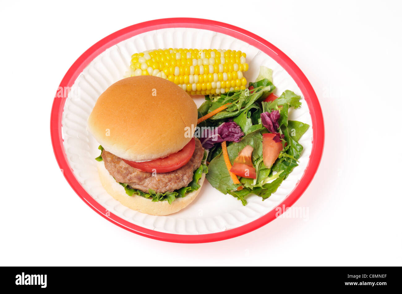 Turkey burger with lettuce and tomato in bread roll in red retro plastic basket with corn on the cob and salad on - Stock Image