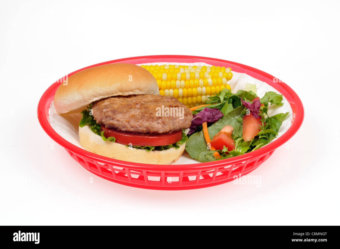 Turkey burger with lettuce and tomato in bread roll in red retro plastic basket with ear of corn and salad on white - Stock Image
