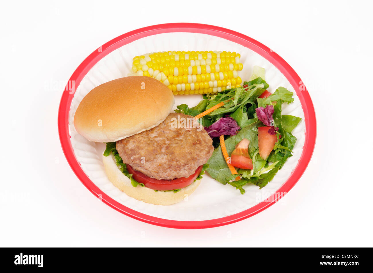 Turkey burger with lettuce and tomato in bread roll with ear of sweet corn and salad in red retro plastic basket - Stock Image