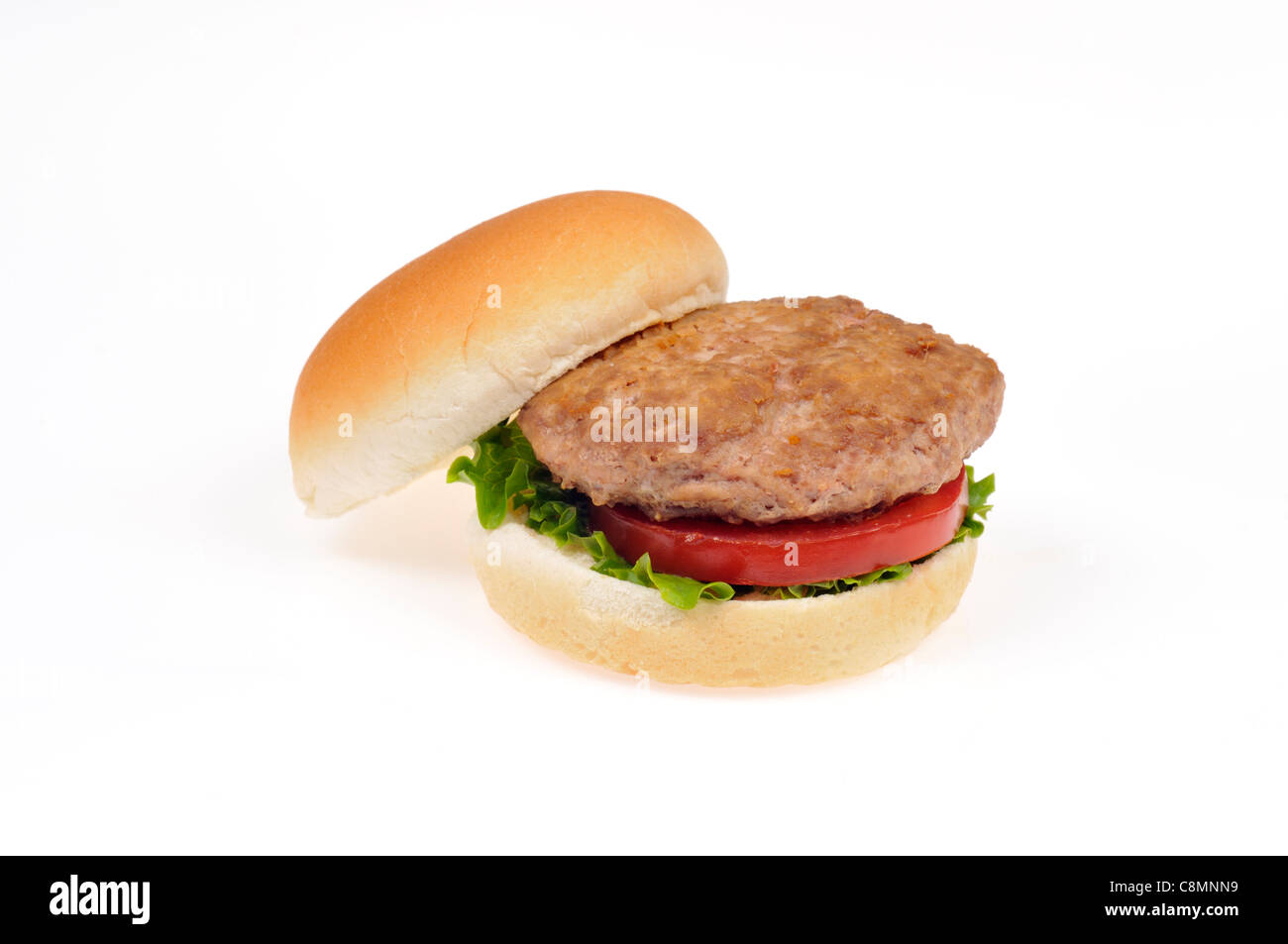 Open turkey burger with lettuce and tomato in bread roll on white background cutout. - Stock Image