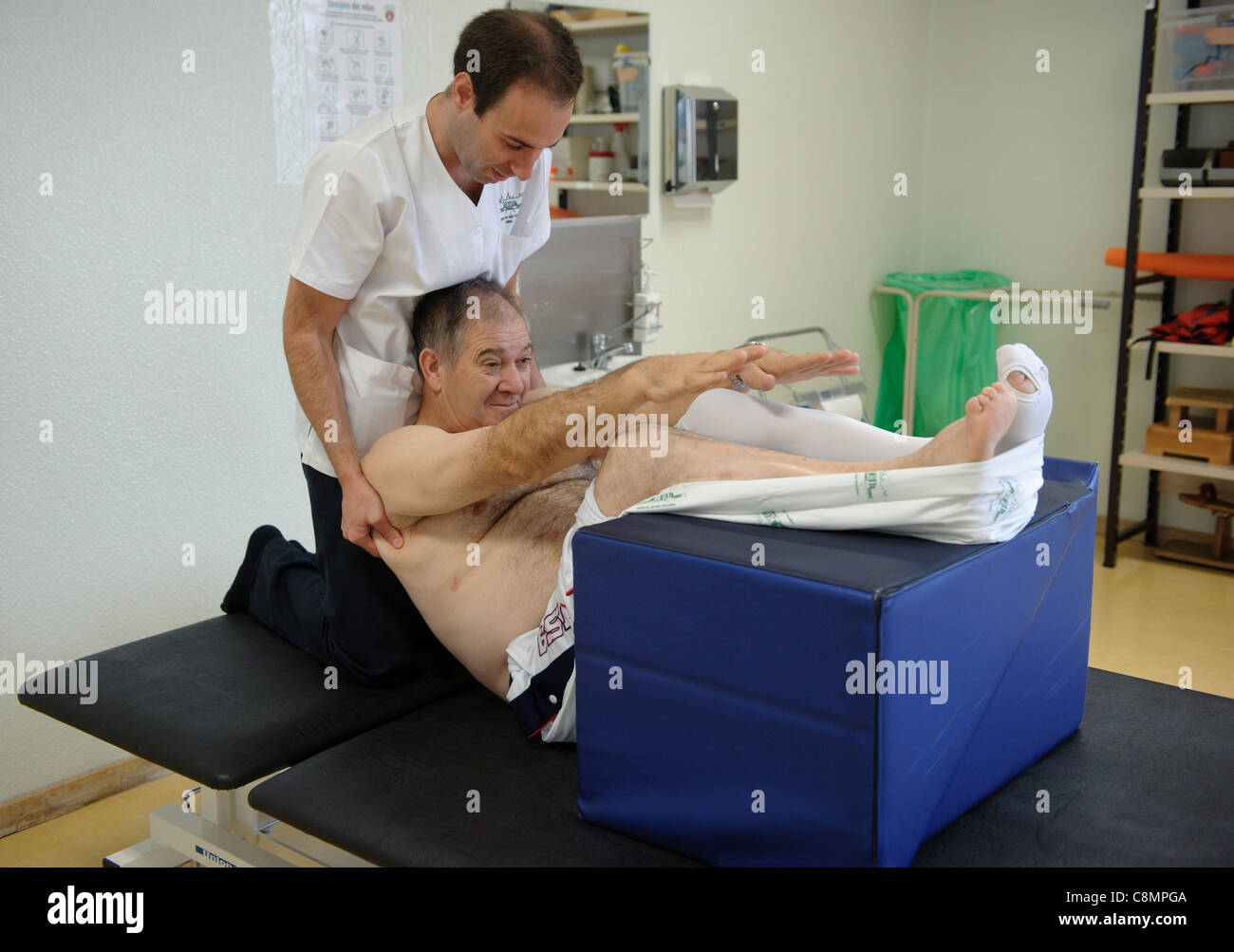 Male physiotherapist helping a patient do an exercise - Stock Image