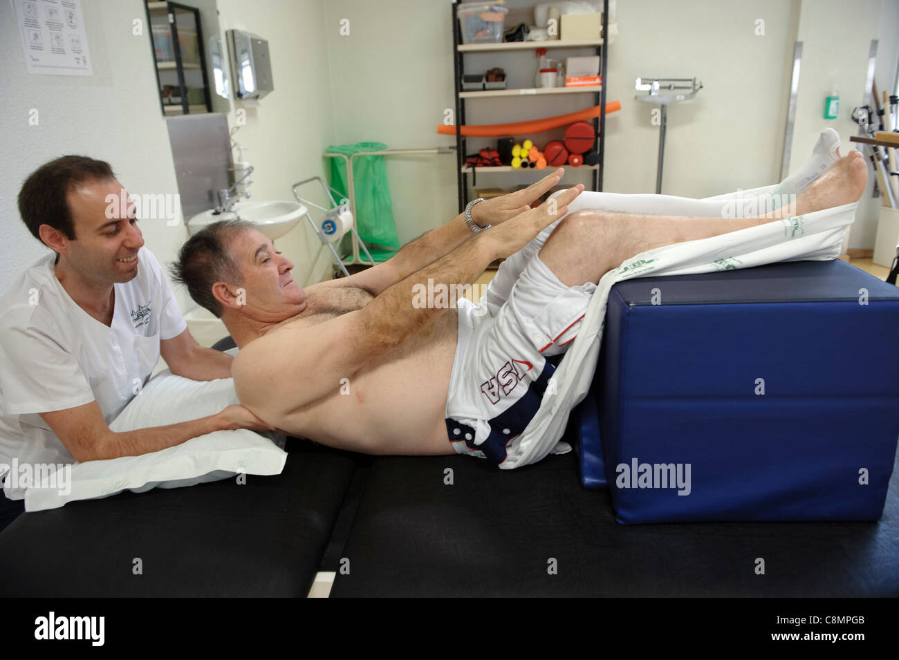 Physiotherapist helping a patient do an exercise - Stock Image