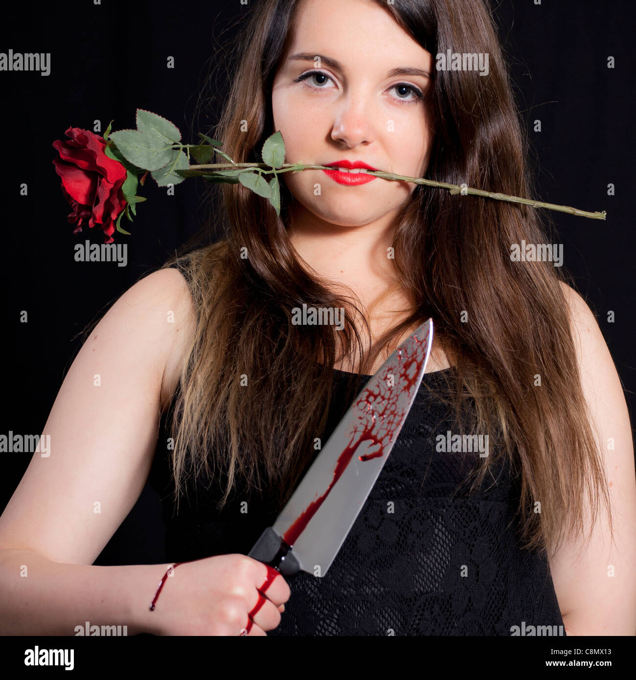 young woman with a bloody knife and a red rose - Stock Image