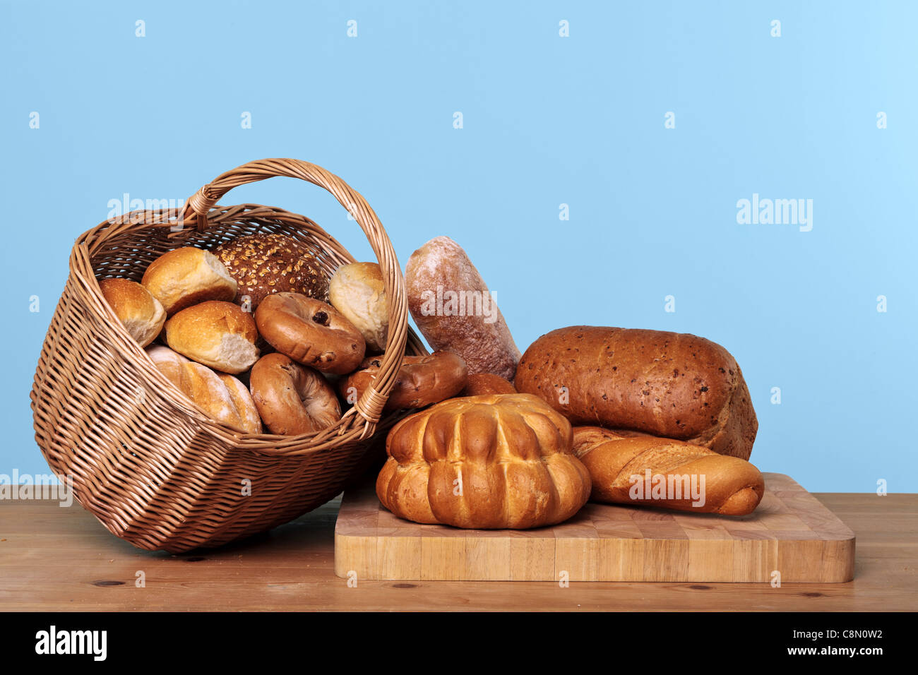 Photo of various types of bread loaves and rolls in a wicker basket on a wooden table with blue background. - Stock Image