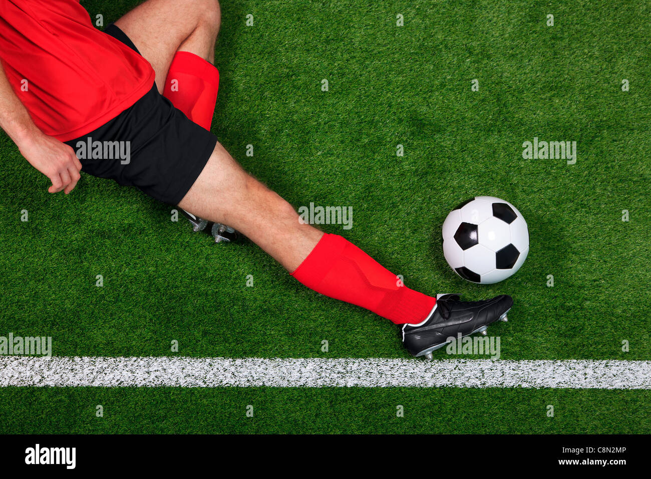 Overhead photo of a football or soccer player sliding in to save the ball going over the sideline - Stock Image