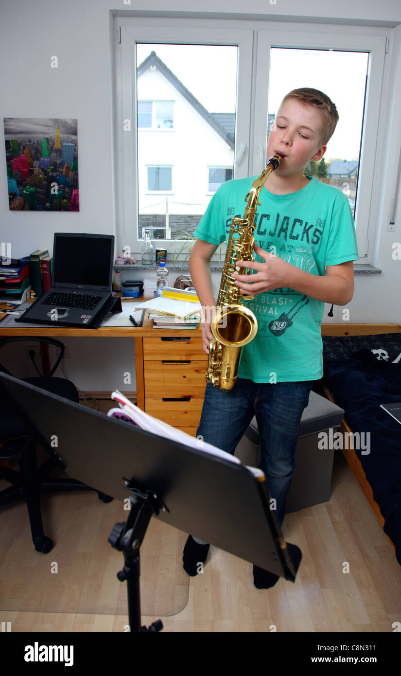 Boy, 13 years old, exercise with his saxophone, at home. - Stock Image