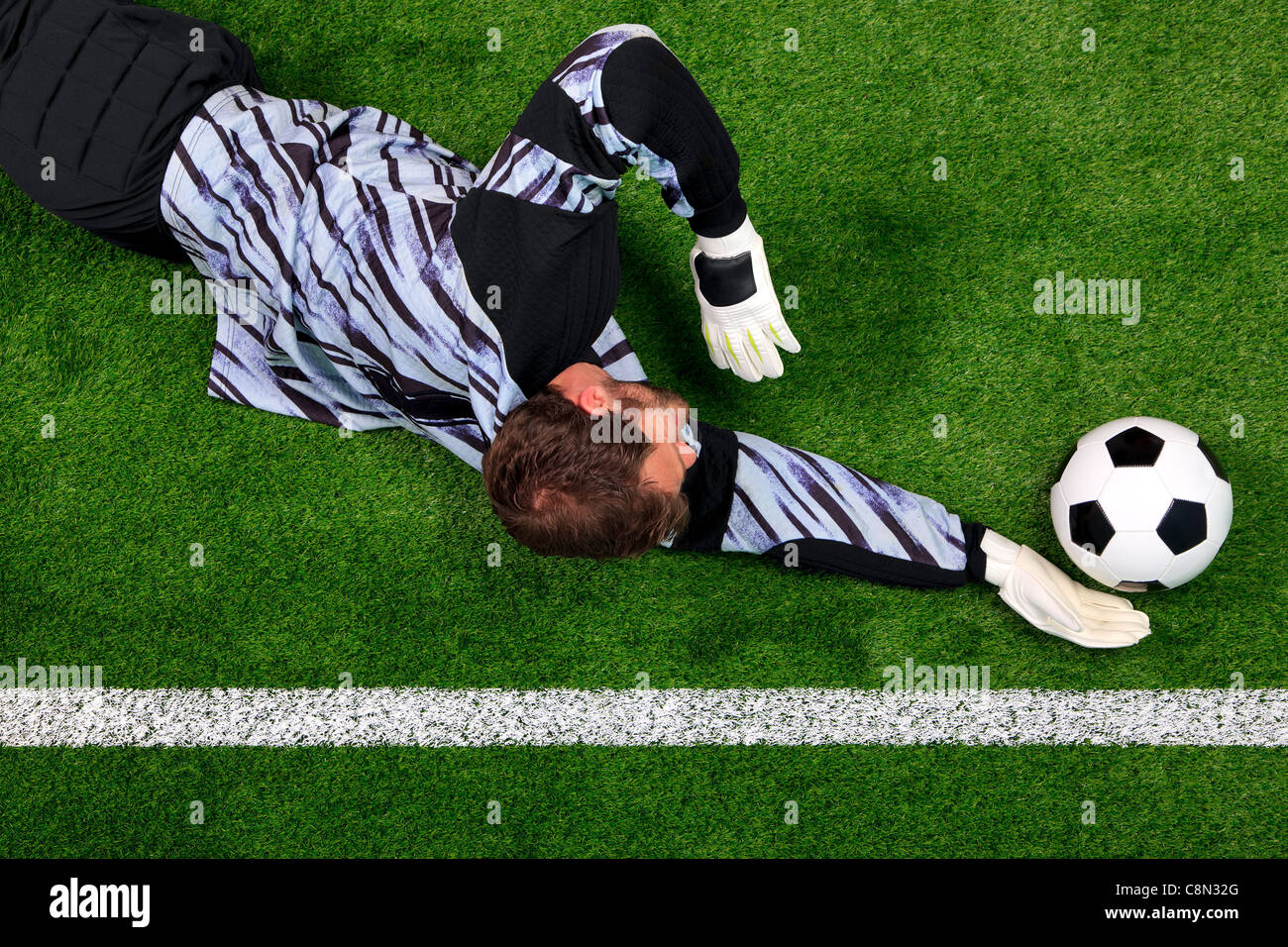 Overhead photo of a football goalkeeper diving to save the ball from crossing the goal line. - Stock Image