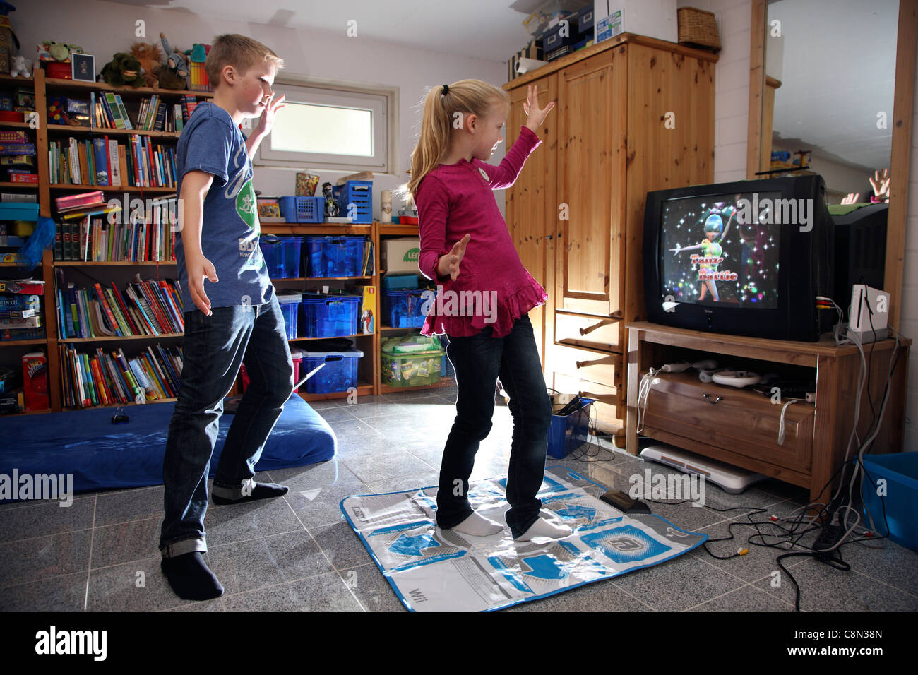 Two kids, girl 10 and boy 13 years old, playing at home with a WII video game. - Stock Image