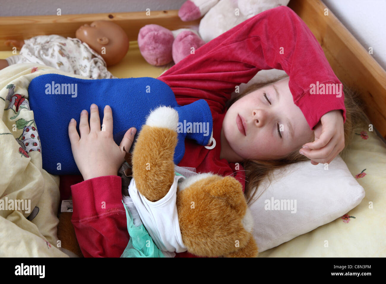 Young girl, 10 years old, lies in bed, at home, sick with a cold. Using a hot-water bag, accompanied by some cuddly - Stock Image