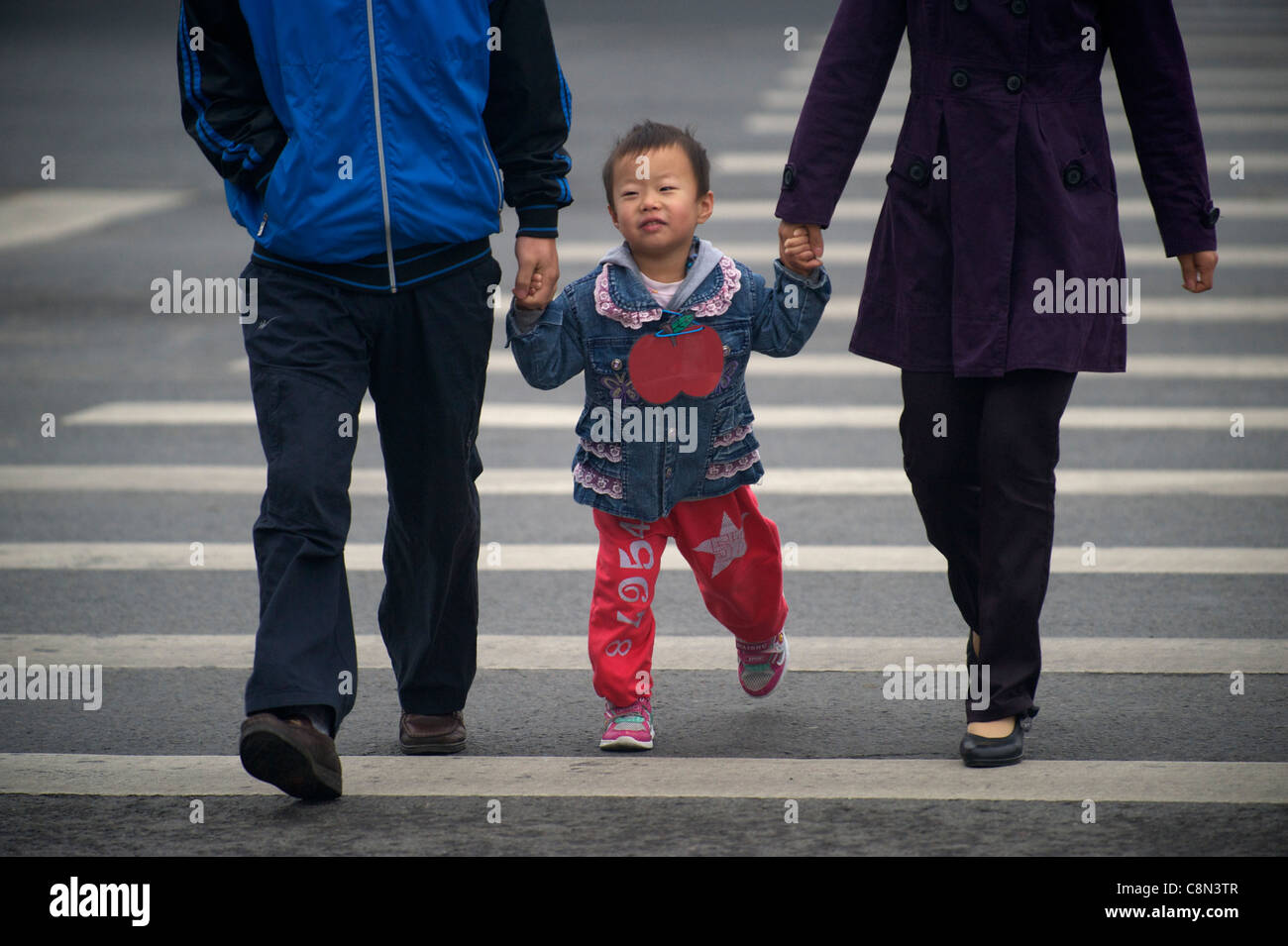 A Chinese girl holds parent's hands crossing a street in Beijing, China. 20-Oct-2011 - Stock Image