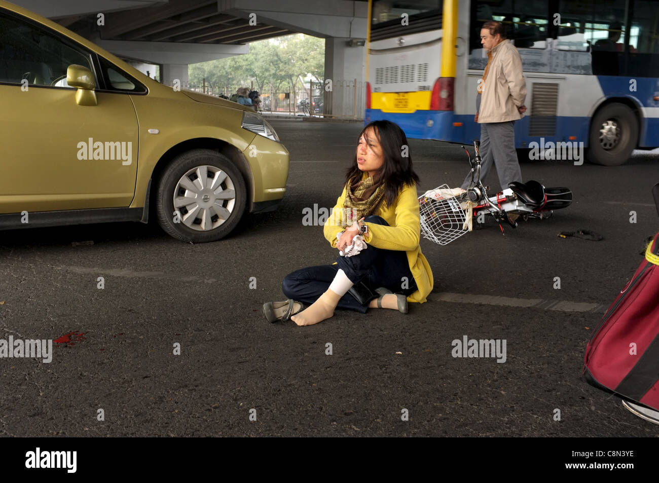 A woman sits on the ground after her bicycle was hit by a car during a traffic accident in Beijing, China. 20-Oct - Stock Image