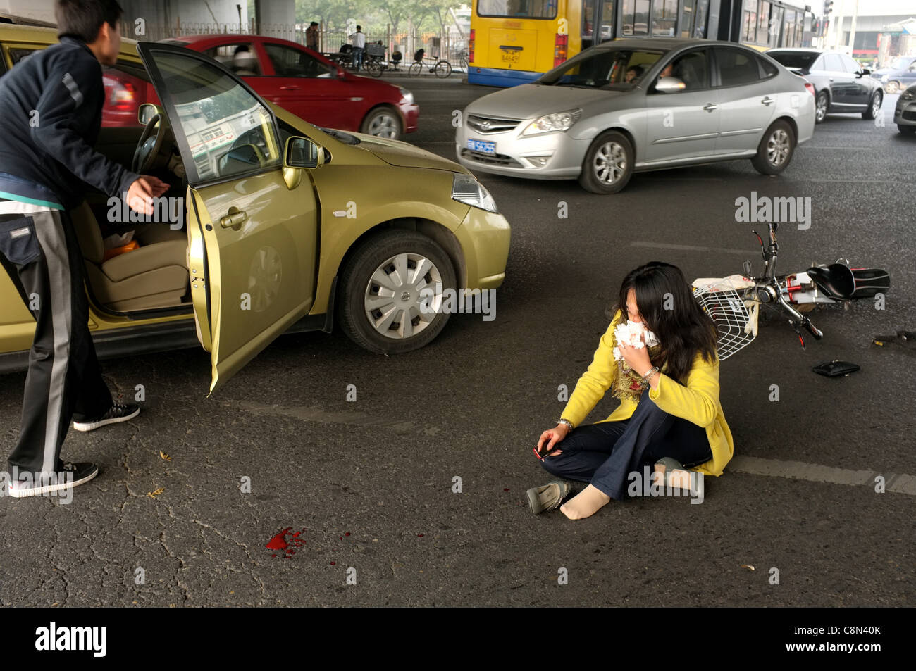 A woman sits on the ground after her bicycle was hit by a car while the driver tries to close the car door during - Stock Image
