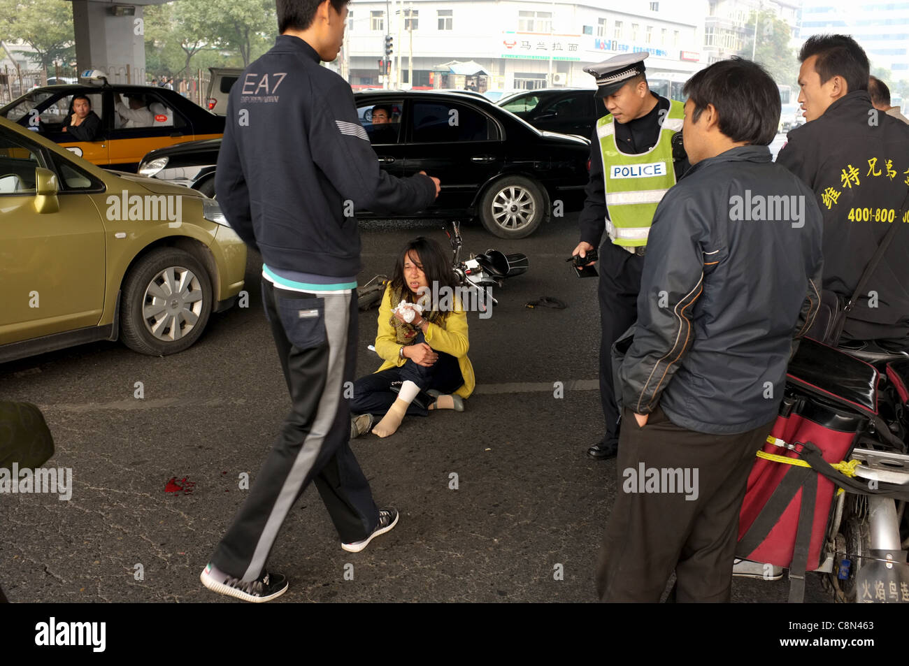 A woman sits on the ground while a policeman and the driver standing aside during an accident in Beijng, China in - Stock Image