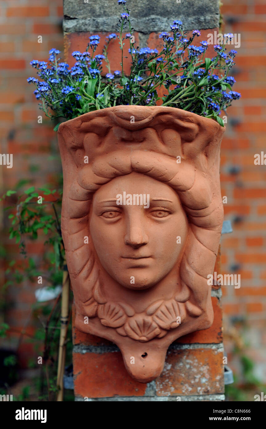 terracotta pot face woman Victorian style imitation plant holder fixed attached to red brick wall blue flower bloom - Stock Image