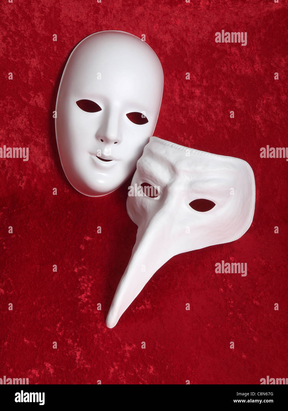 2 white masks on red velvet background - Stock Image