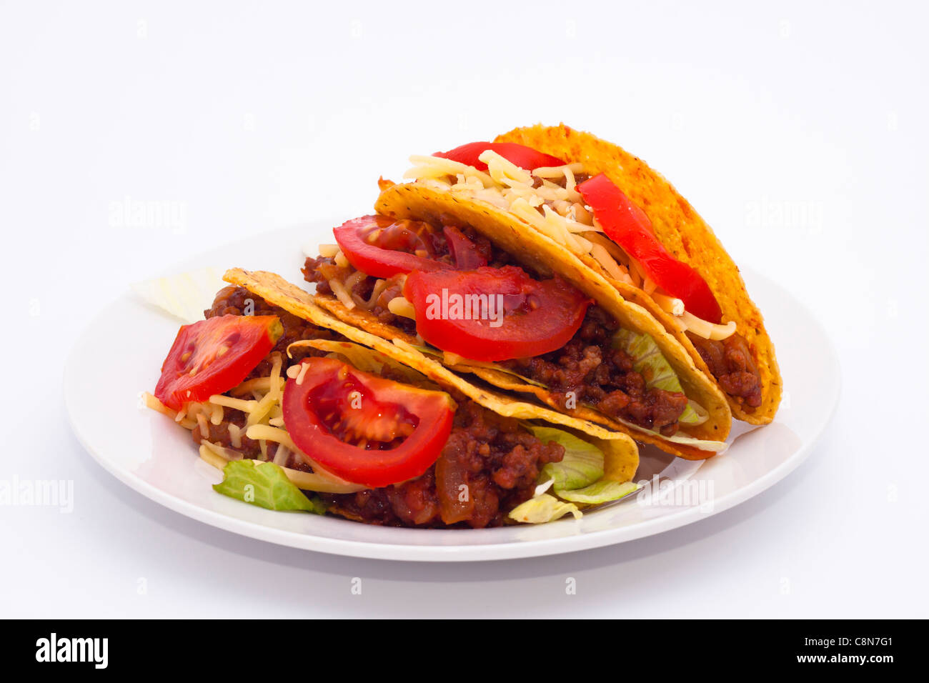 Delicious Mexican tacos on plate, isolated on white background. - Stock Image