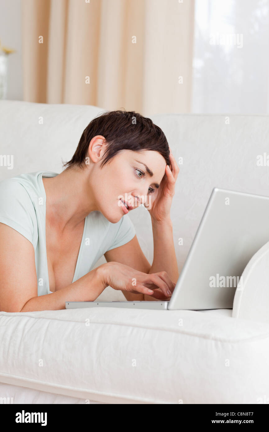 Tired young woman using a laptop Stock Photo