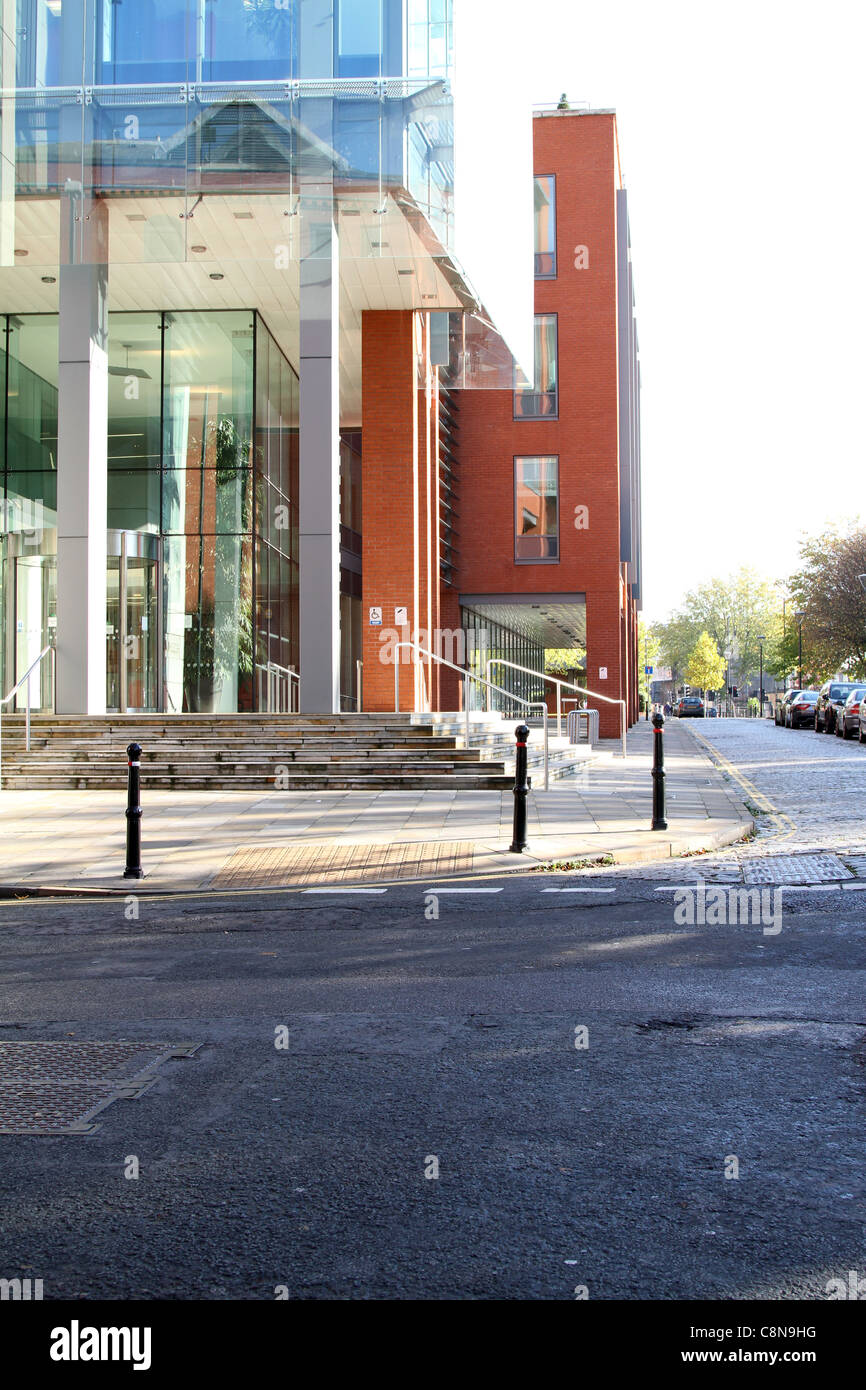Outside an office block, paved sidewalk that passes under the buildings square archway, road to the foreground - Stock Image