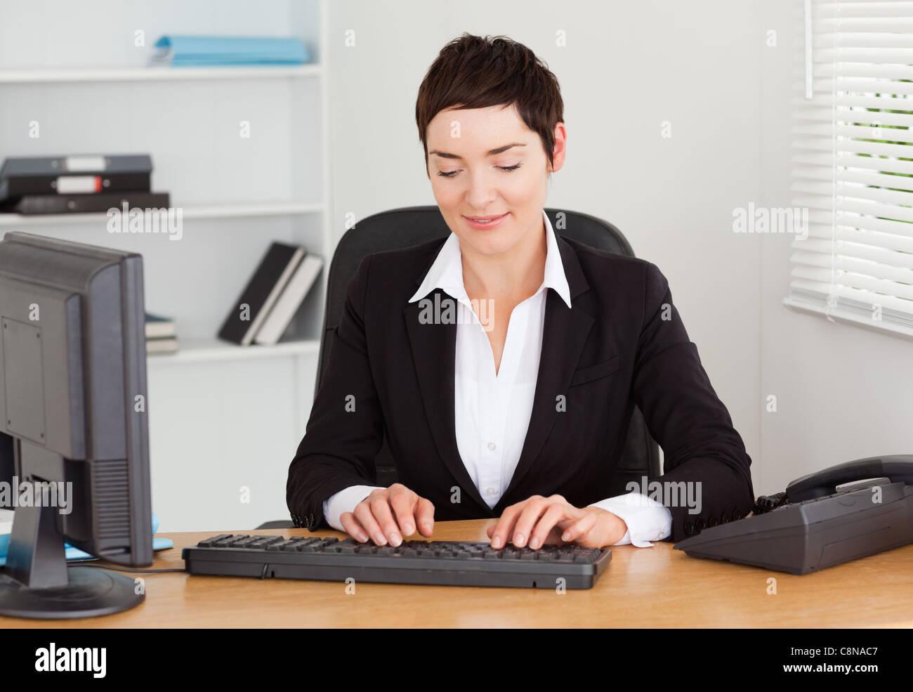 Secretary typing on her keybord - Stock Image