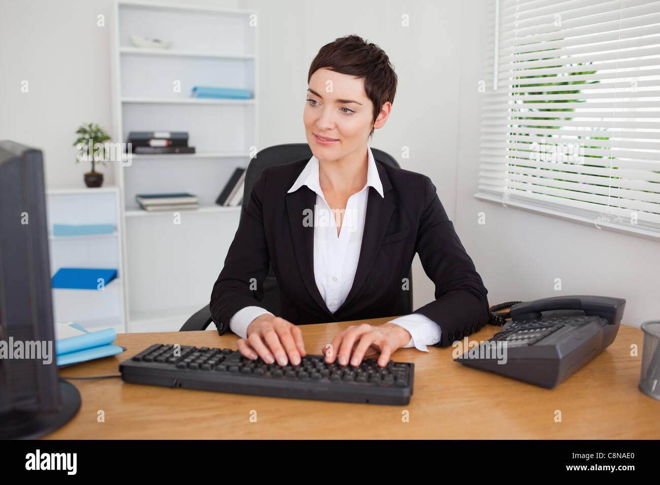 Charming secretary typing on her keybord - Stock Image