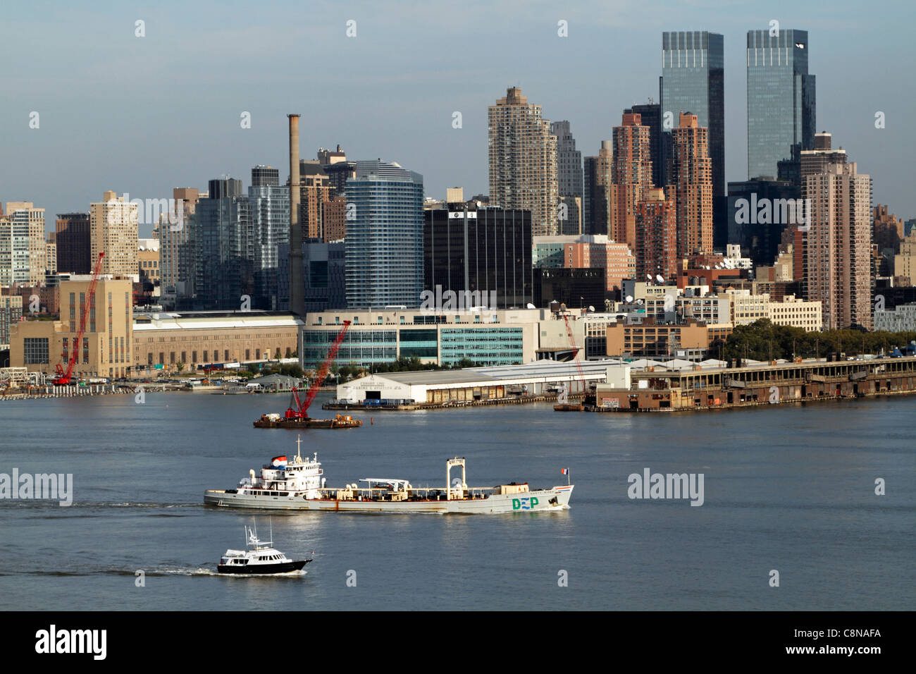 Boats on the Hudson River passing passing Manhattan skyline. - Stock Image