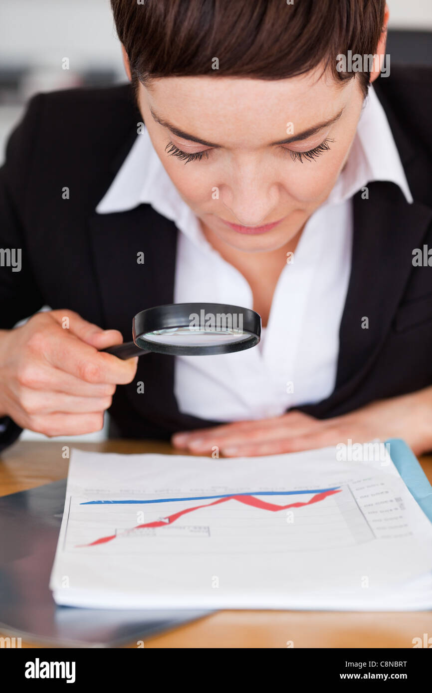 Businesswoman looking at a chart with a magnifying glass - Stock Image
