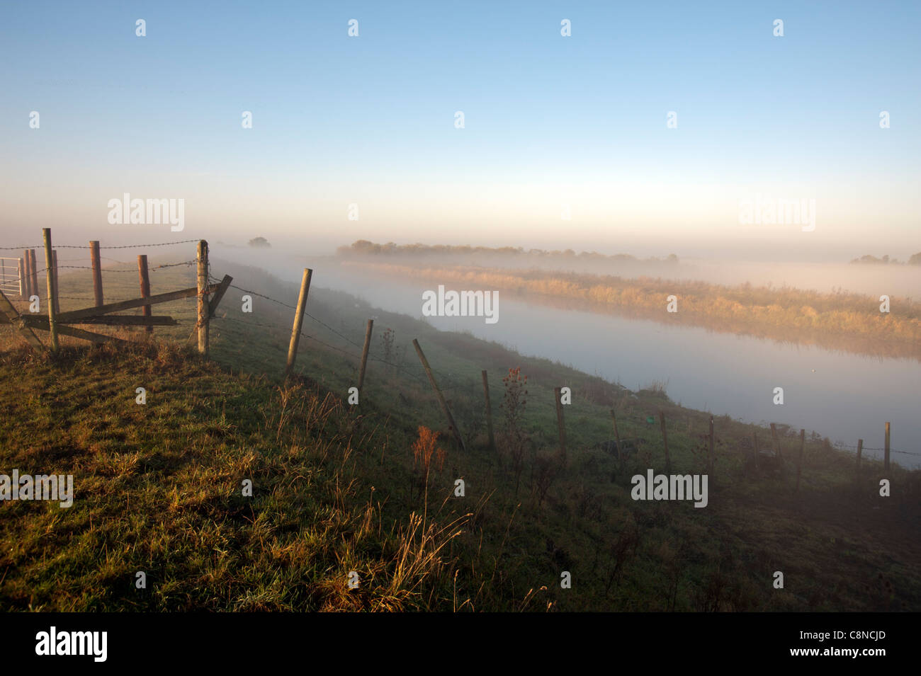 The old Bedford Level or River in the Fens near Cambridge, Cambridgeshire on a misty moning - Stock Image