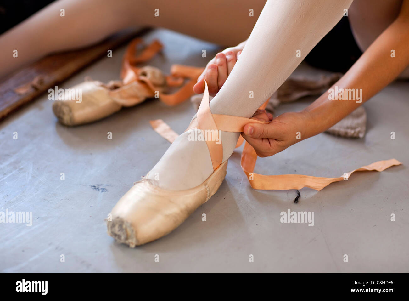Female dancer fastening shoe laces in
