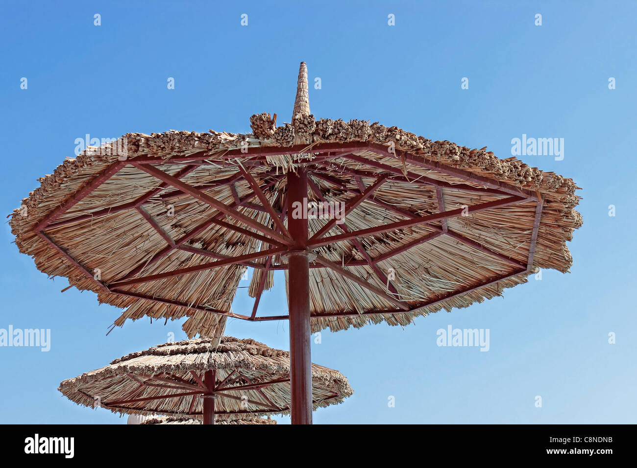 Poolside steel and reed sunshade/parasol against clear blue sky - Stock Image
