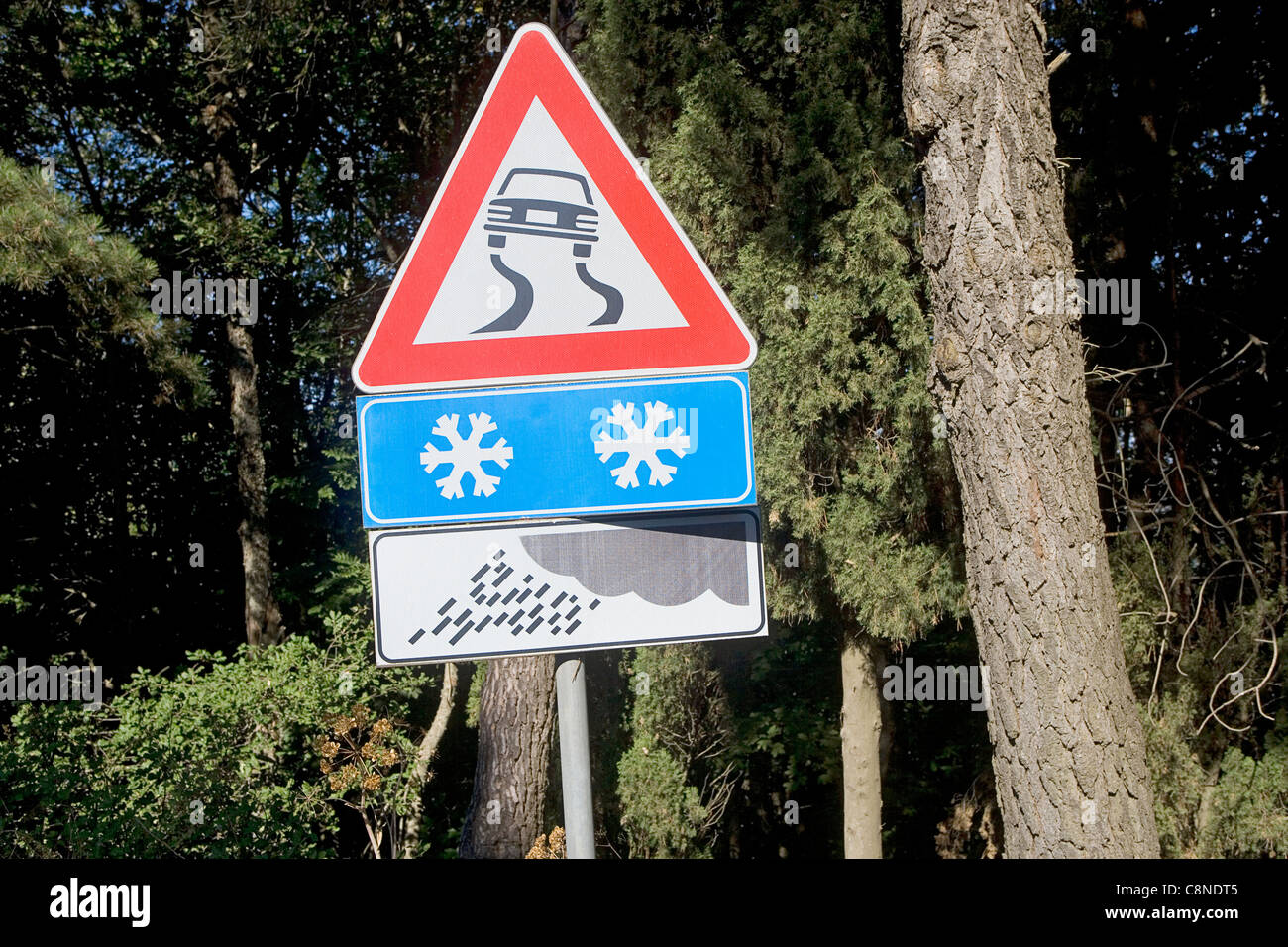 Italy, snow and slippery road warning signs - Stock Image