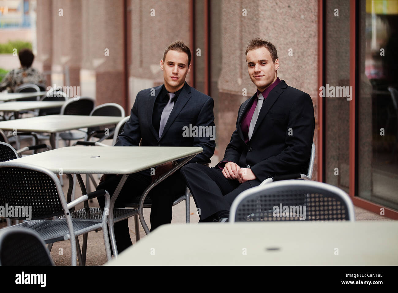 Wide view of two sharp dressed young businessmen at an outdoor cafe in a downtown metropolitan area. Stock Photo
