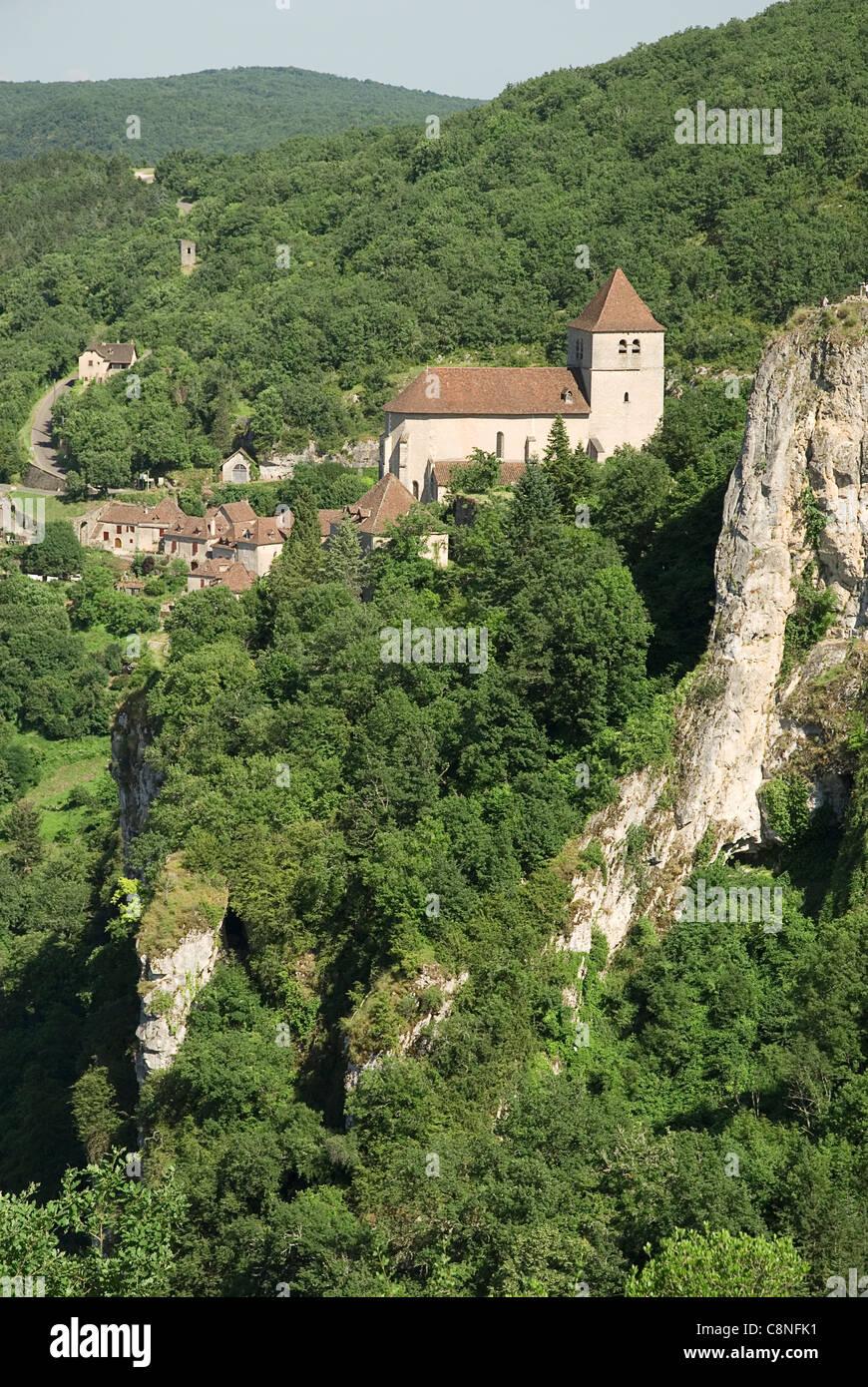 France, Lot, St Cirq-Lapopie, village and church on tree-covered hillside - Stock Image