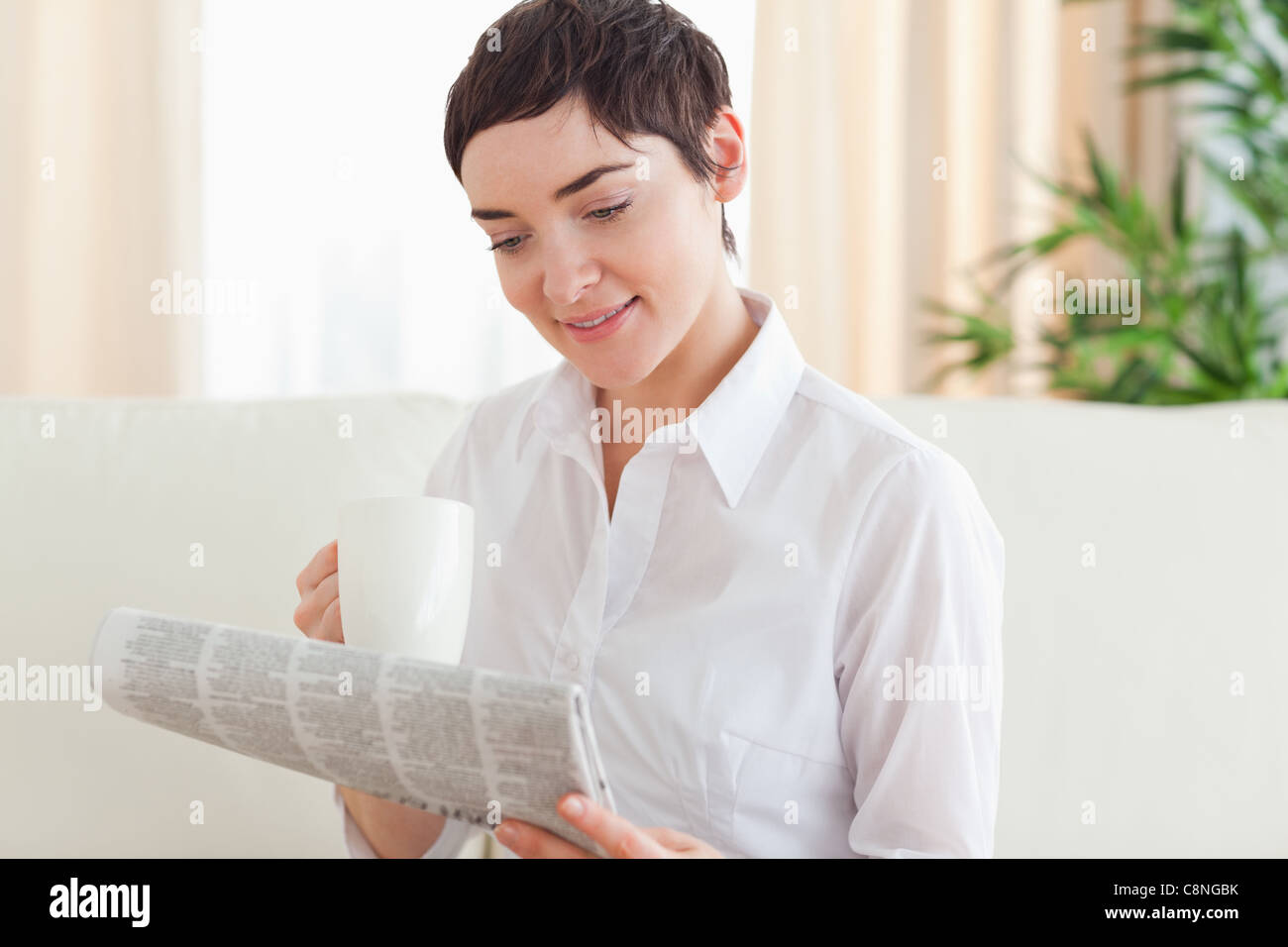 Brunette woman with a cup and a newspaper - Stock Image