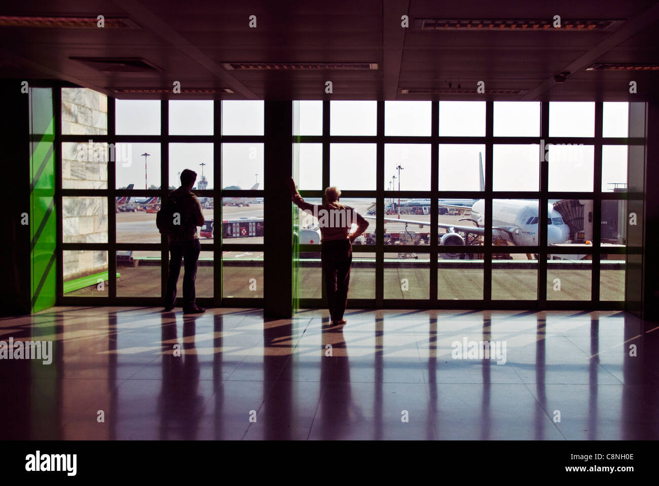 Passengers look out onto aircraft at Milan Linate Airport - Stock Image
