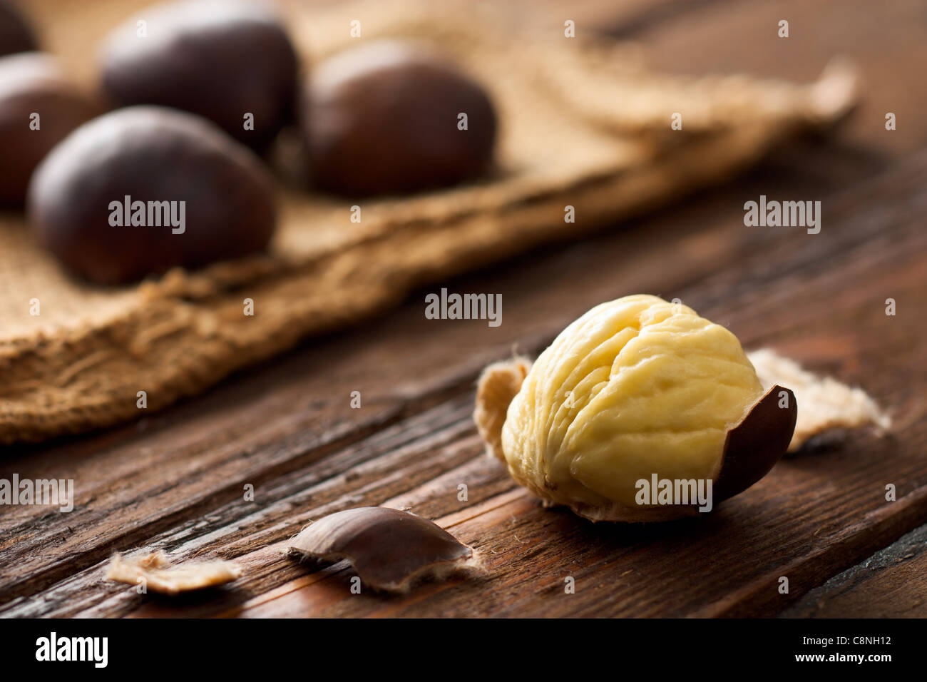 Raw Chestnuts on Wood with Jute - Stock Image