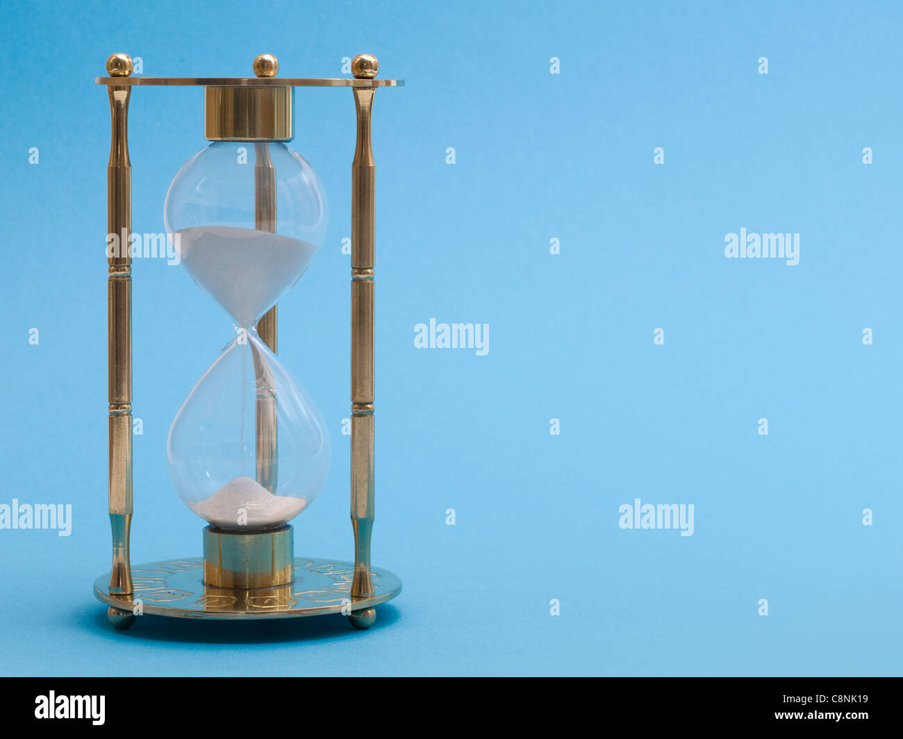 Detail photo of a golden sand glass in front of a blue background Stock Photo