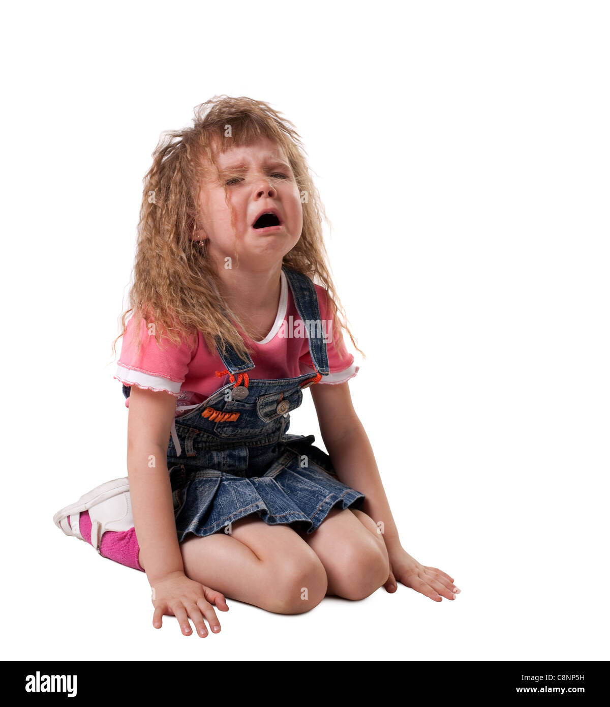 crying kid sit on white, jeans cloth - isolated - Stock Image