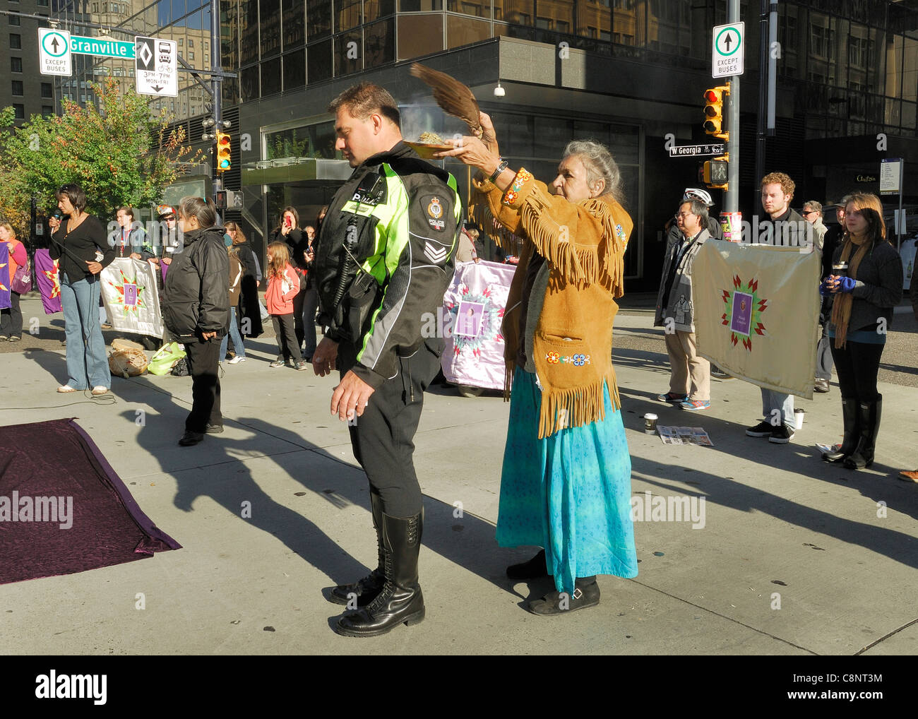 First Nations female elder performing a smudging ceremony on a Vancouver Policeman. - Stock Image