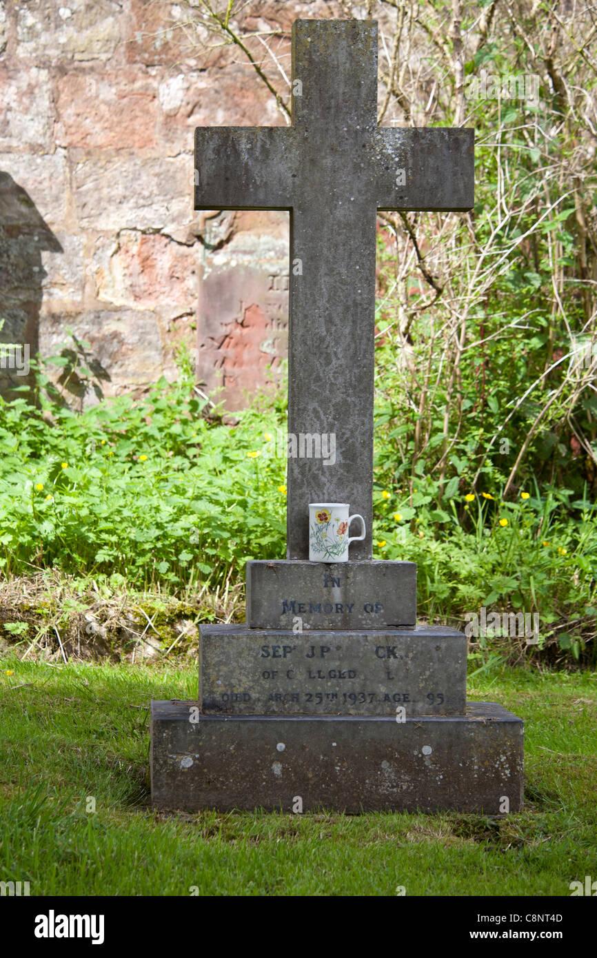 A crucifix headstone in churchyard with a tea mug left on the bottom ledge - Stock Image