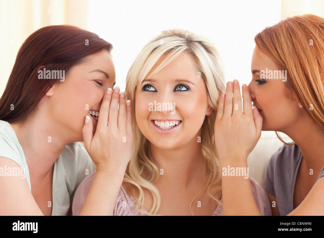 Young woman being told two secrets at a time - Stock Image
